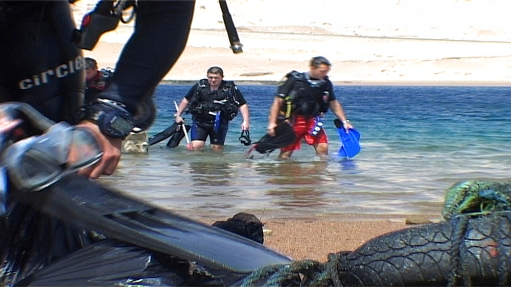 Rubbish on sand. Divers emerge from sea nearby.  Red Sea. Egypt