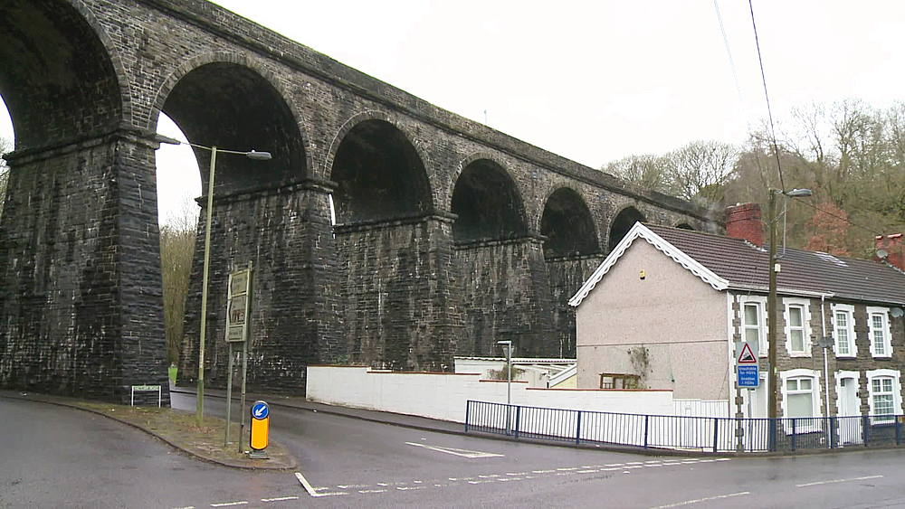 (wide shot) viaduct next to terraced houses, South Wales Valleys, Wales, United Kingdom