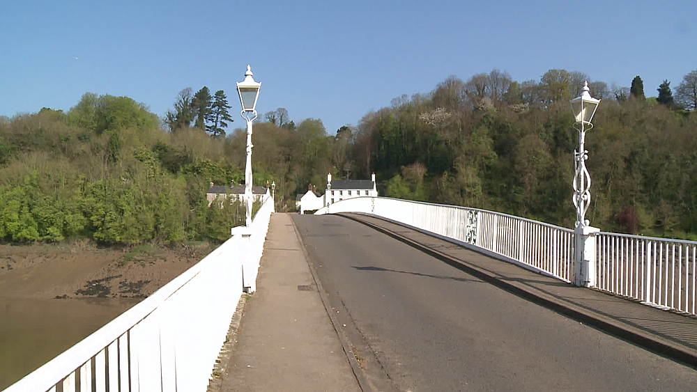 (medium wide shot) & (wide shot) of white bridge over Wye with woman walking dog & traffic, Chepstow, Wales, United Kingdom, Europe
