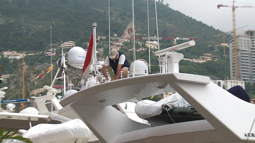 crew cleaning yacht medium shot po & wide shot with harbour