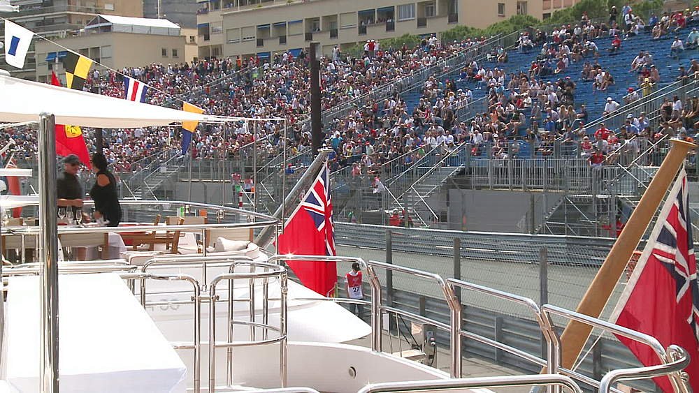 wide shot people on yacht, fans in stadia, cars whizz by