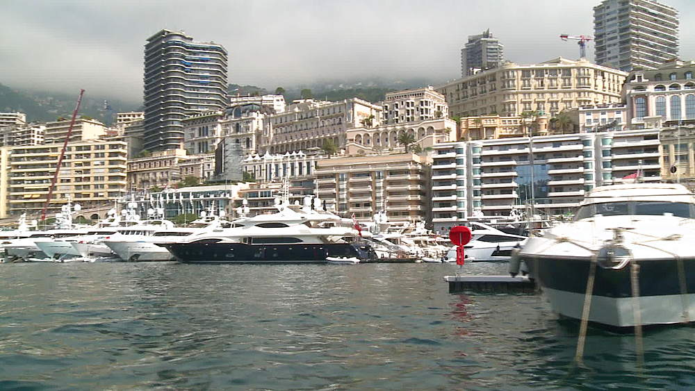 tracking ws pov of moored yachts with grand prix stadium behind