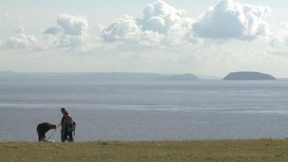 ms dog walkers on headland sea & island behind - 1031-2213