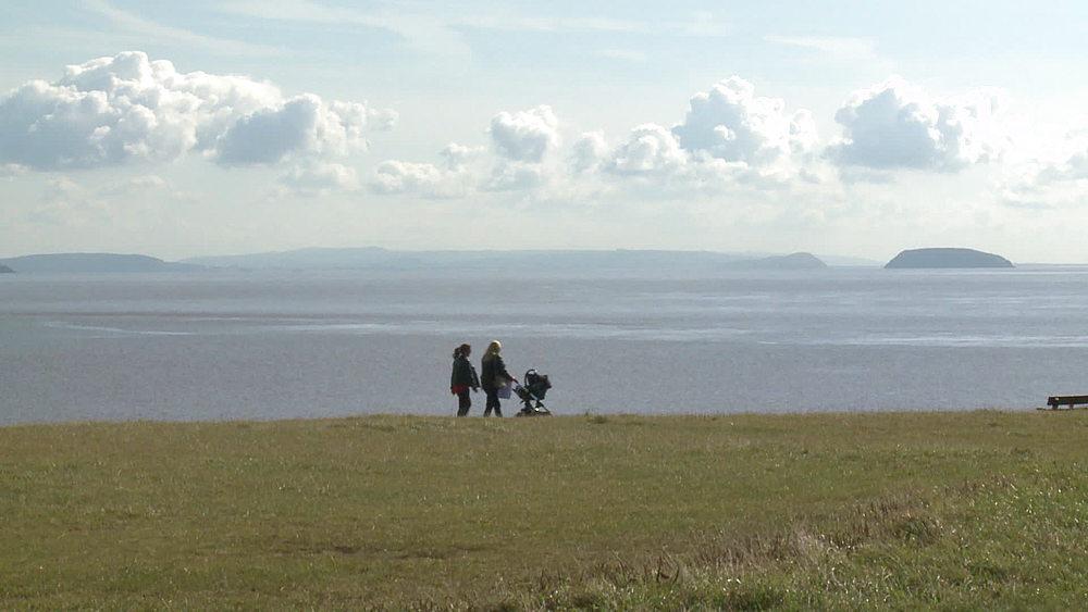 ws walkers pushing pramon headland sea & island behind - 1031-2229