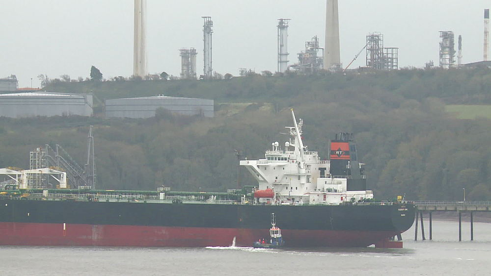 Tanker discharging water boat alongside refinery, Milford Haven, Wales, United Kingdom (medium-shot) - 1031-2264