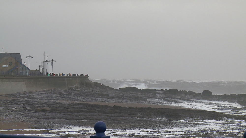 People on sea wall & stormy sea, Porthcawl, Wales, United Kingdom (medium-wide-shot & pull to wide-shot)
