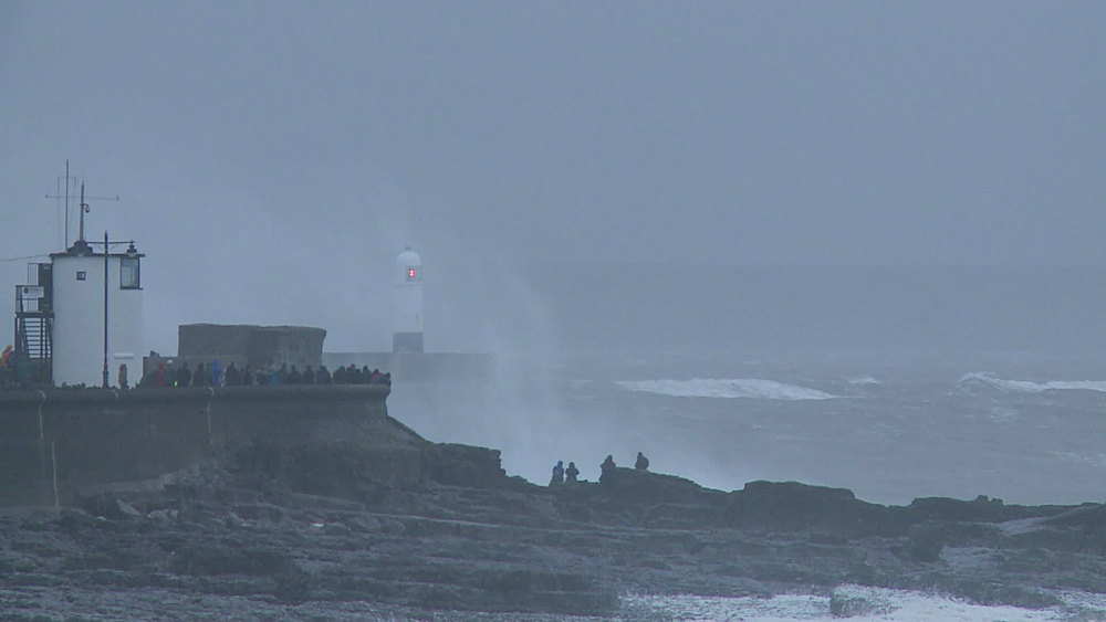 Lighthouse and sea wall with people and breaking waves, Porthcawl, Wales, United Kingdom (wide-shot) - 1031-2273