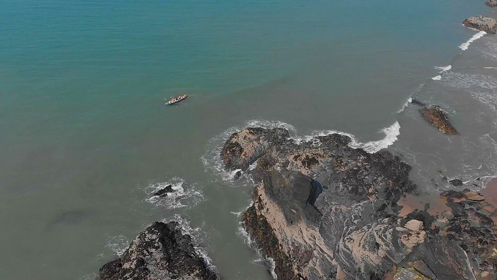 drone aerial shots of cliff, beach, sea , sea rowers in boat  & town
