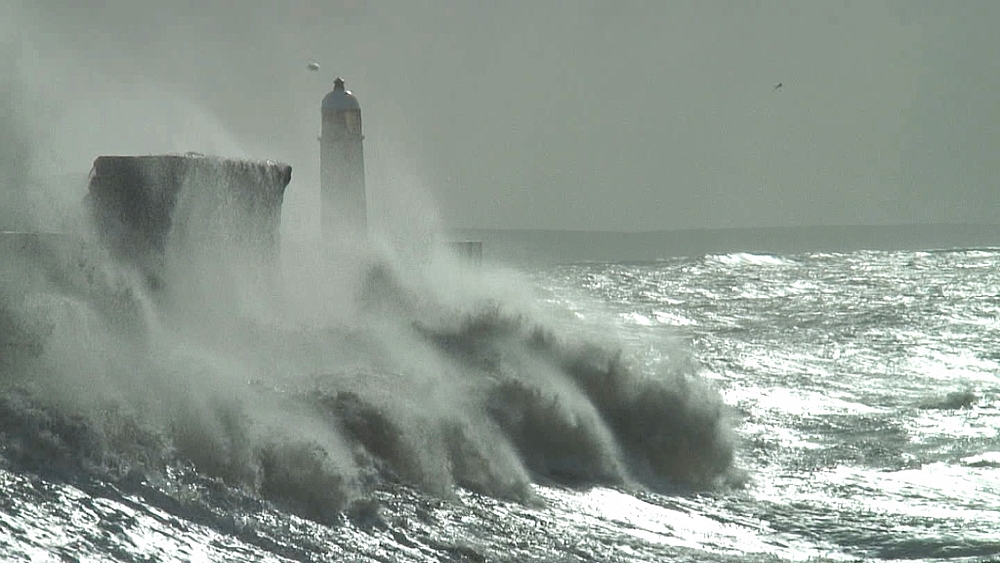 Sea defences and storm waves over pier with lighthouse at end. Porthcawl. Wales. UK