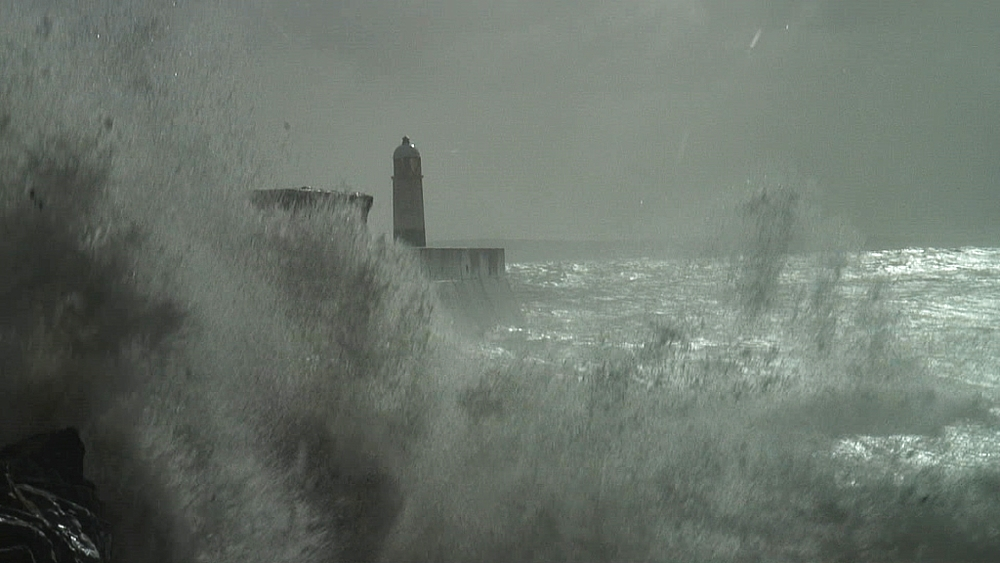 Sea defences and storm waves over pier with lighthouse at end.Porthcawl. Wales. UK