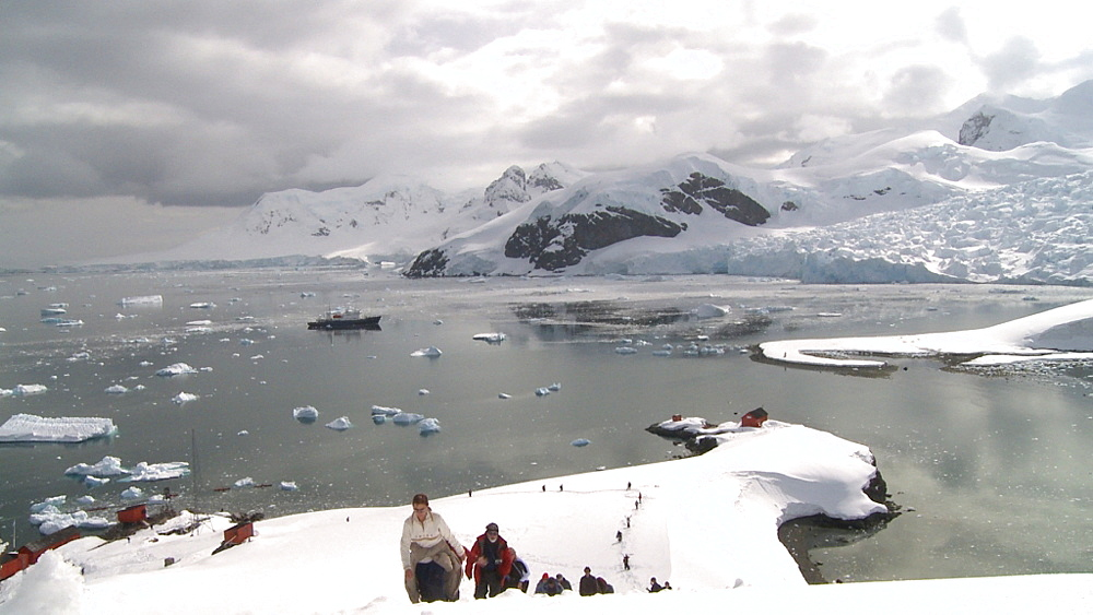 Argentinian Antarctic station from high angle with hikers moving up to camera. Almirante Brown. Paradise Bay