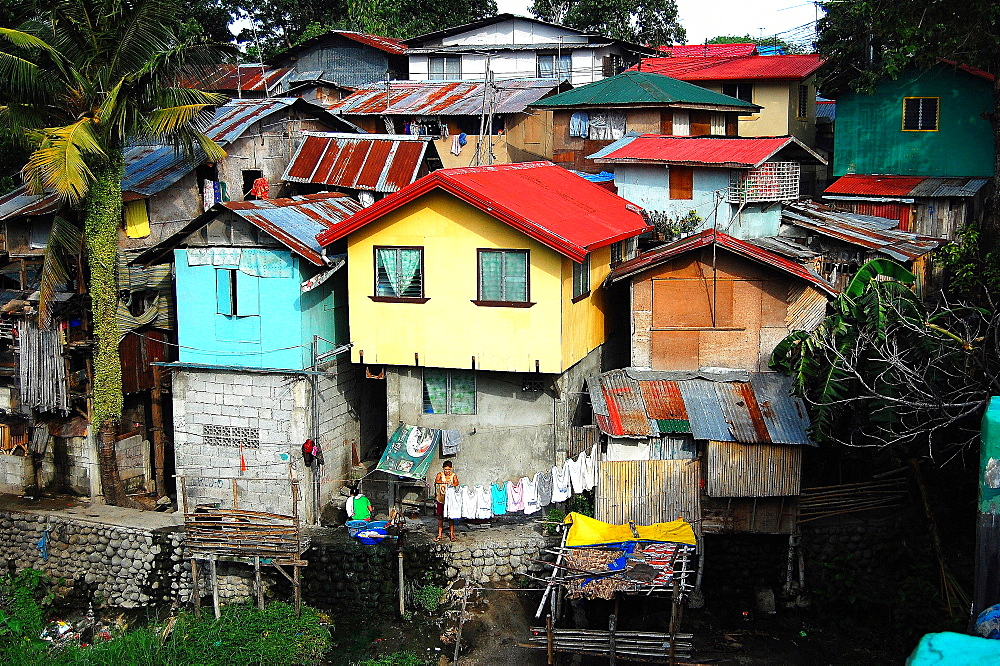 LIFE IN A SLUM AREA. a woman hangs her laundry in front of her house in a slum area.  Bacolod City.  Philippines.