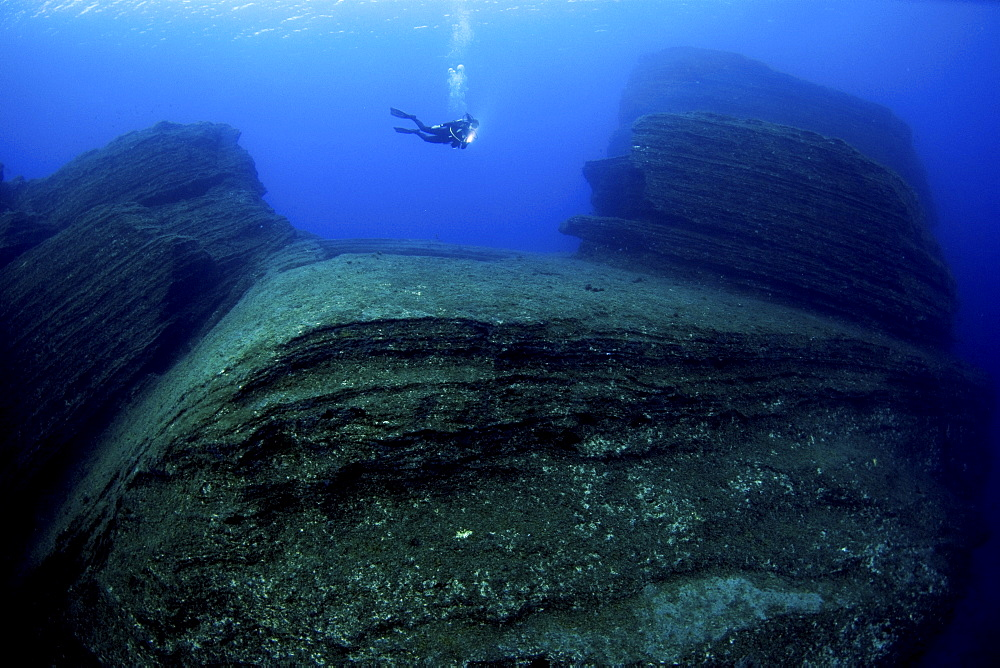 Diver in volcanic formations, El Hierro, Canary Islands