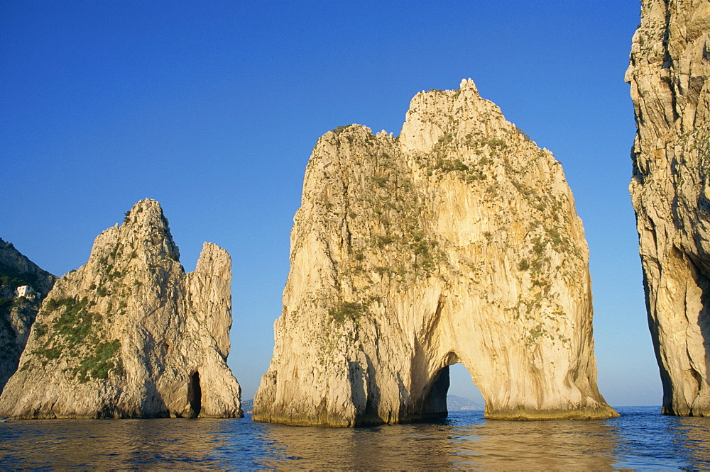 Rock arches known as the Faraglioni Stacks off the coast of the island of Capri, Campania, Italy, Europe