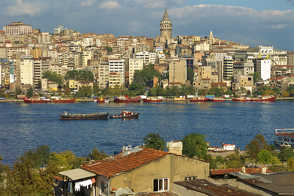 Boats on the Golden Horn, with apartment blocks, commercial buildings and the Galata Tower beyond in Istanbul, Turkey, Europe
