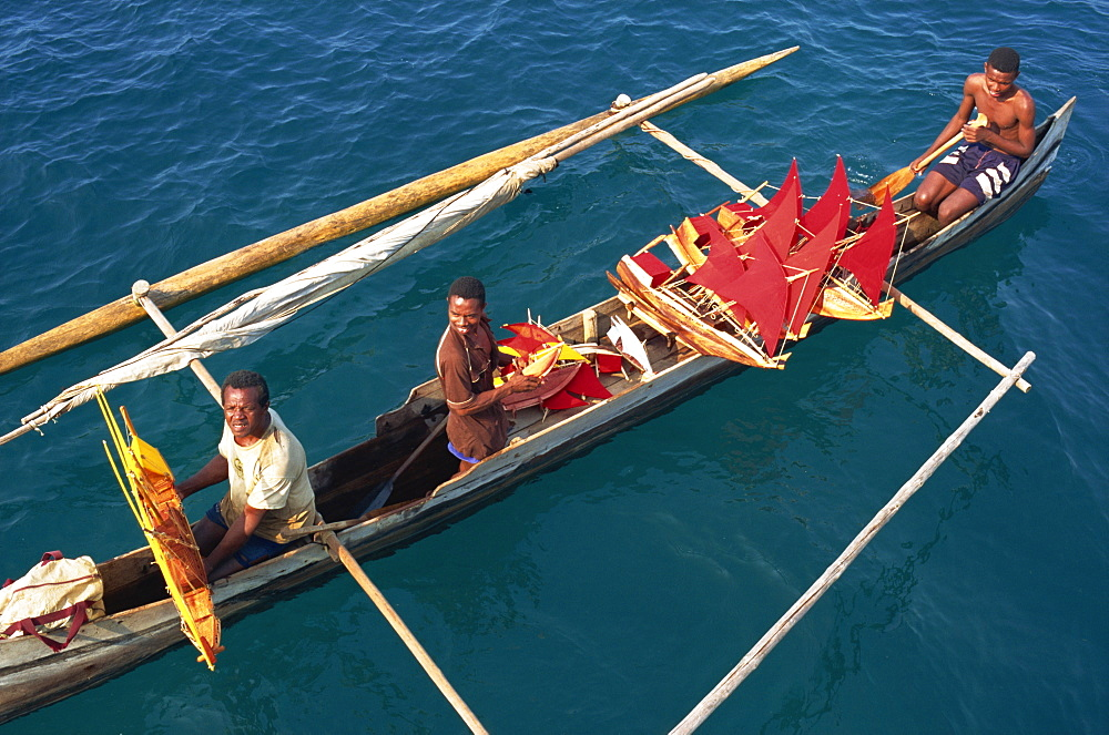Men in outrigger canoes selling model boats with red sails, Nosy Be, Madagascar, Africa - 110-14238