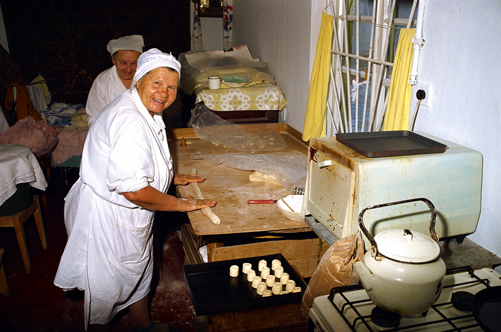 Women making scones in a small home oven in Yalta in the Ukraine, Europe