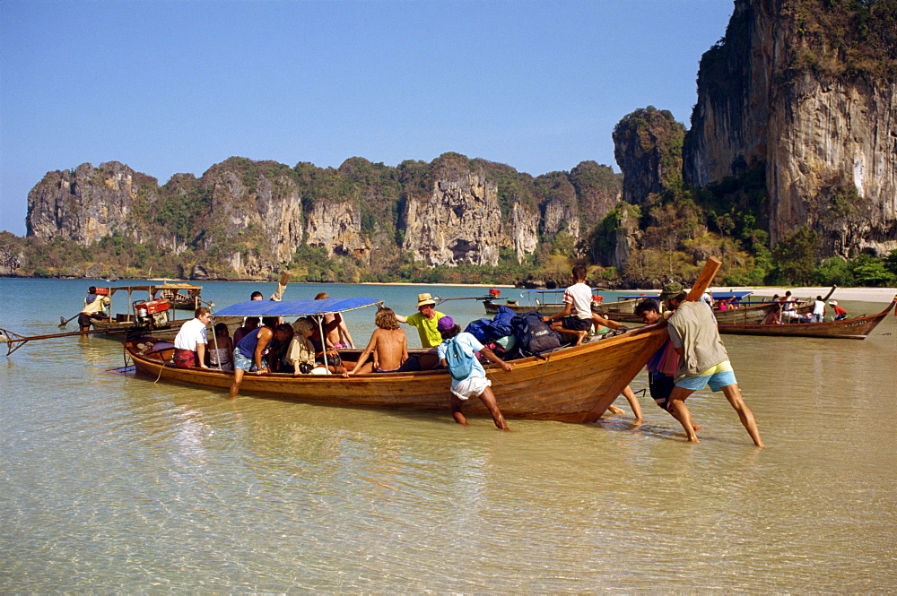 Launching a long tail boat full of backpackers from Railay Beach to Krabi in Thailand, Southeast Asia, Asia