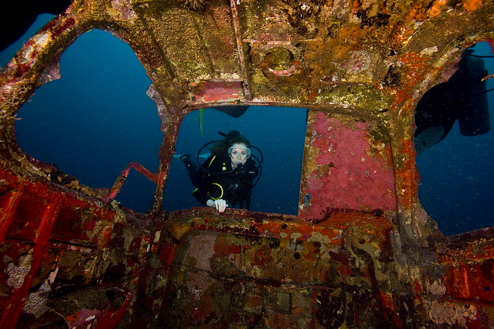 Diver entering the front window of a four seater plane wreck, Philippines, Southeast Asia, Asia