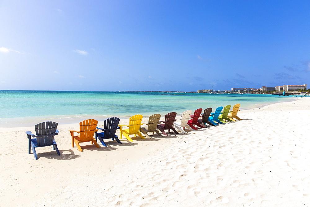 A row of colourful wooden deckchairs on Palm Beach, Aruba, Netherlands Antilles, Caribbean, Central America