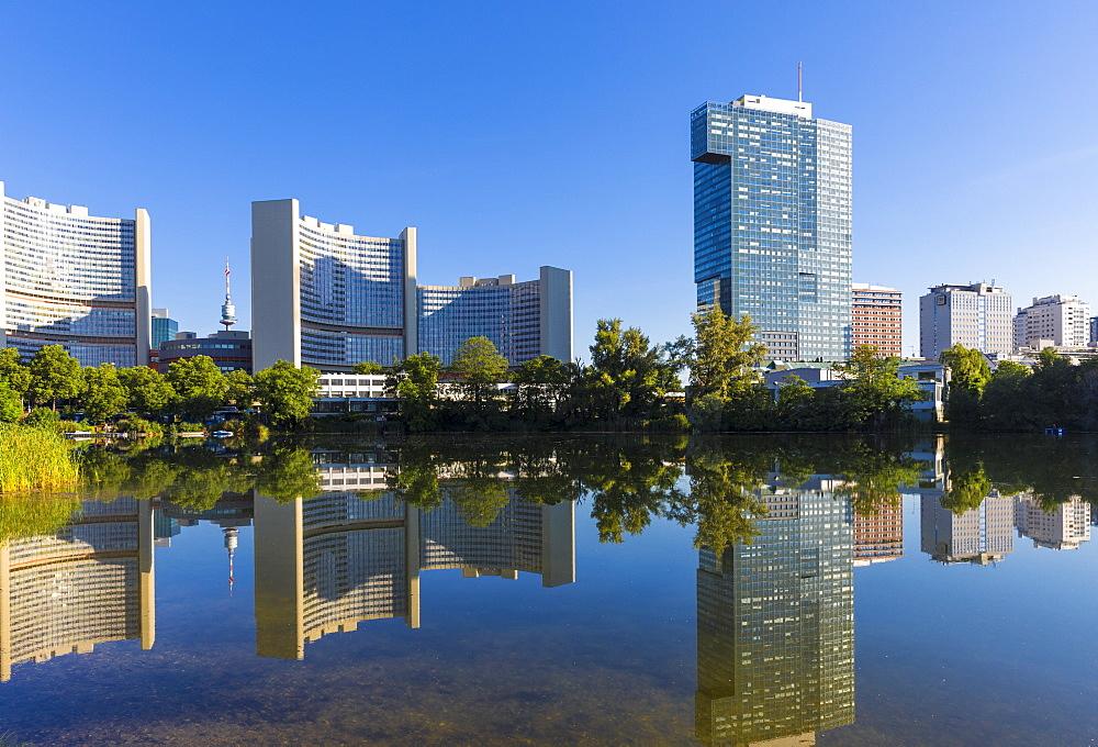 United Nations buildings reflected in lake, UNO City, Vienna, Austria, Europe