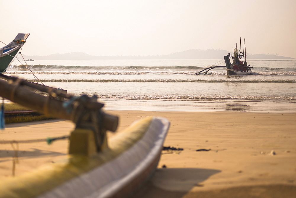 Weligama Beach, a fishing boat returning from sea on the South Coast of Sri Lanka, Indian Ocean, Asia