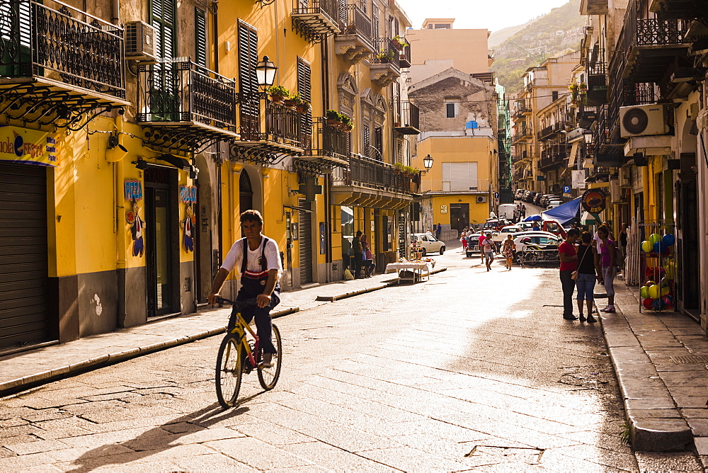 Sicilian man cycling along the main street at sunset, Monreale, near Palermo, Sicily, Italy, Europe