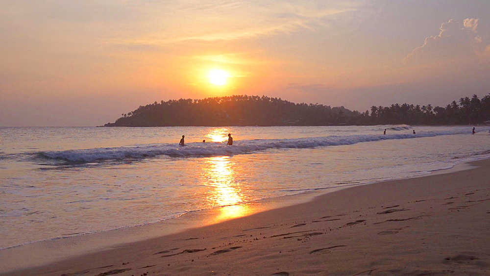 Mirissa Beach, tourist couple on a romantic walk along the beach at sunset, South Coast of Sri Lanka, Asia