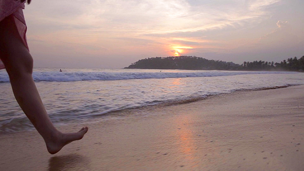 Mirissa Beach, feet of a tourist walking along the beach at sunset, South Coast of Sri Lanka, Asia