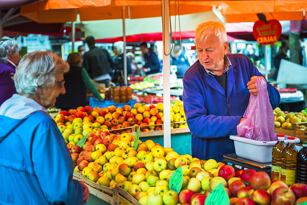 Market stall owner in Ljubljana Central Market on a Saturday in Vodnikov Trg, Ljubljana, Slovenia, Europe