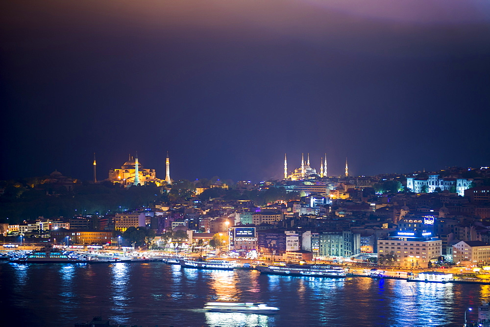Blue Mosque (Sultan Ahmet Mosque) and Hagia Sophia (Aya Sofya) at night seen from The Galata Tower across the Bosphorus Strait, Istanbul, Turkey, Europe
