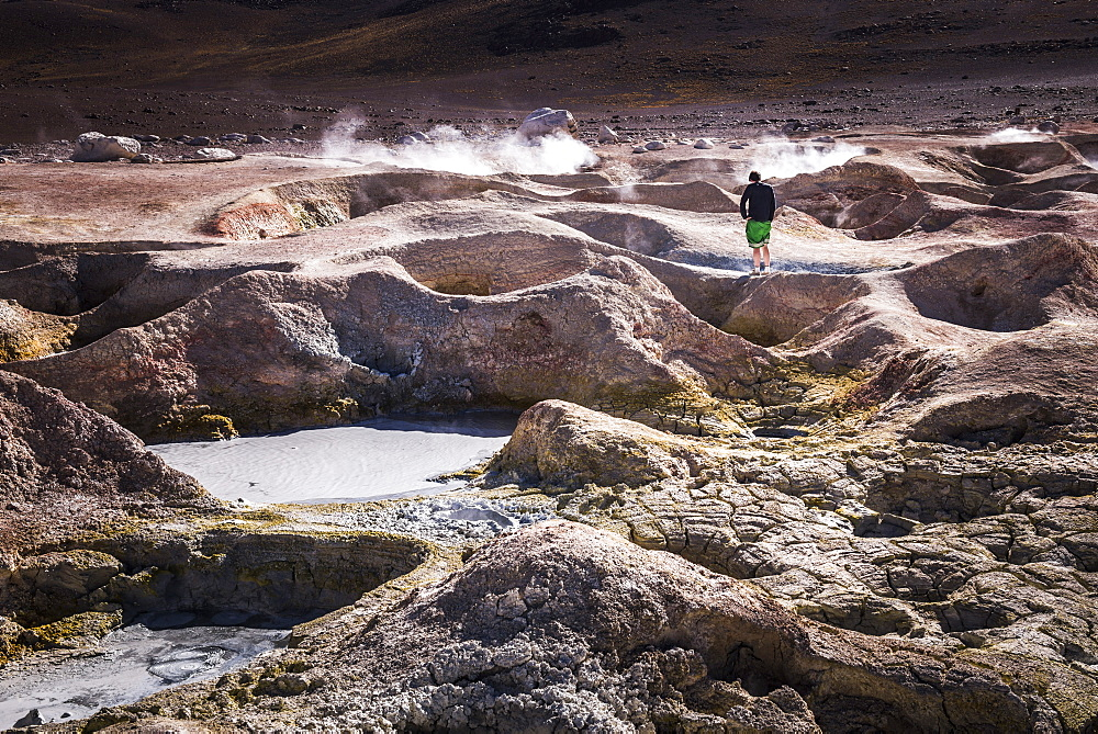 Tourist at Sol de Manana Geothermal Basin area, Altiplano of Bolivia, South America