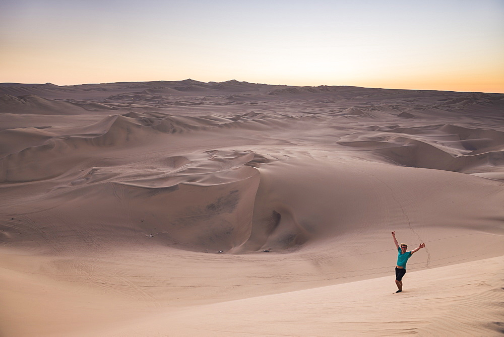 Tourist in the desert at sunset at Huacachina, Ica Region, Peru, South America