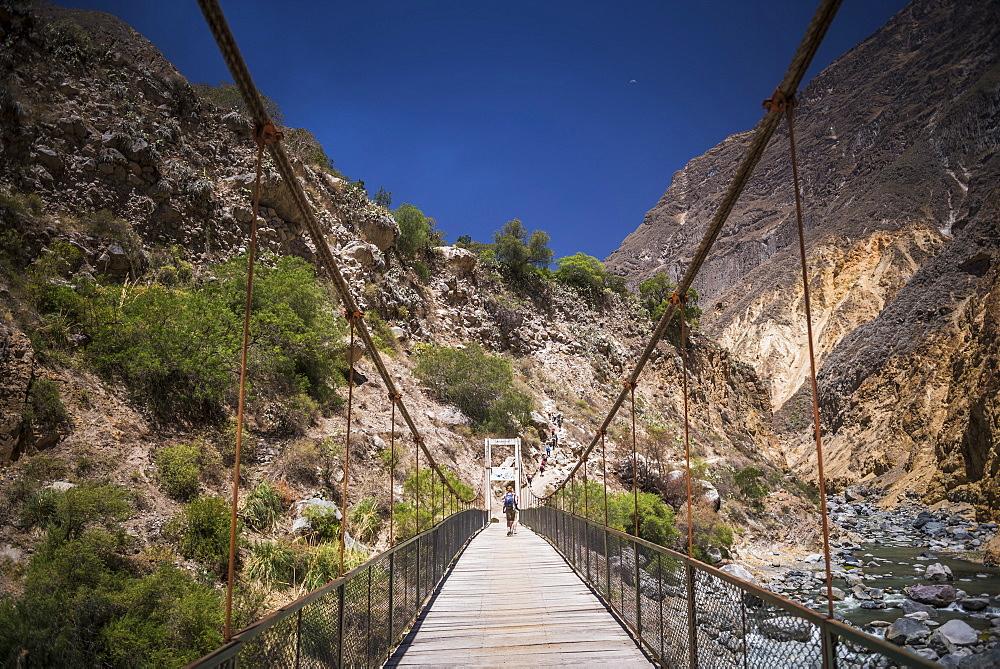 People trekking over Colca River Bridge, Colca Canyon, Peru, South America