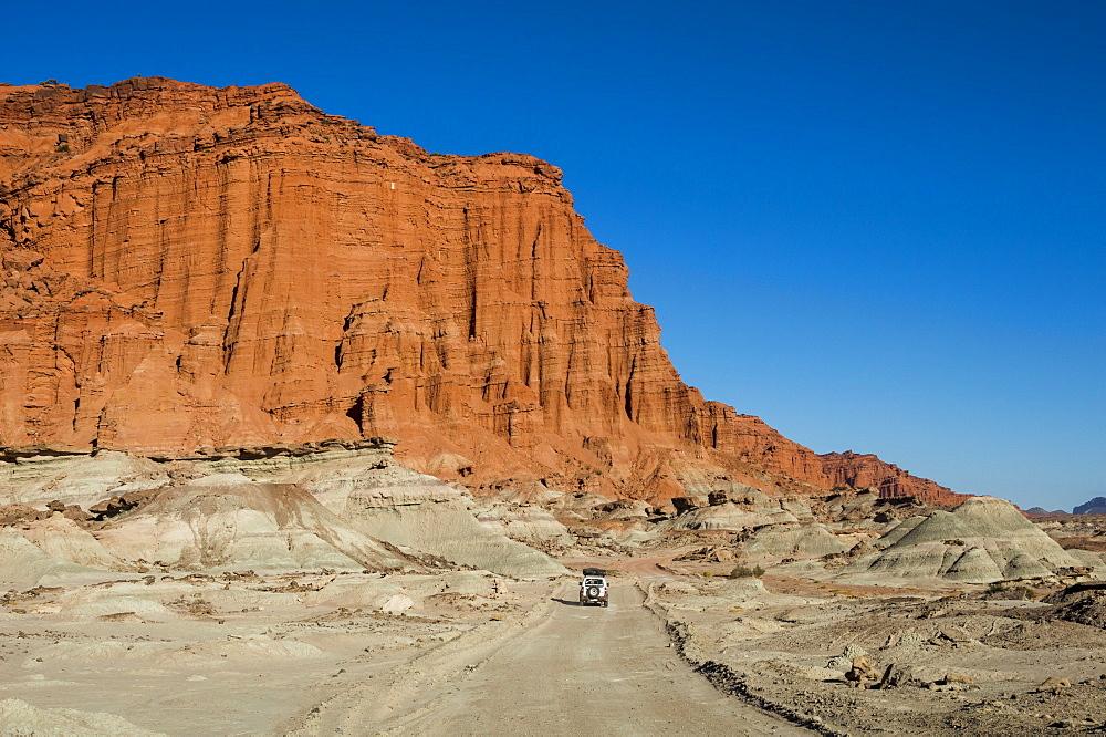 Driving past red Los Coloradas Cliff, Valley of the Moon (Valle de la Luna), Ischigualasto Provincial Park, San Juan Province, Argentina, South America