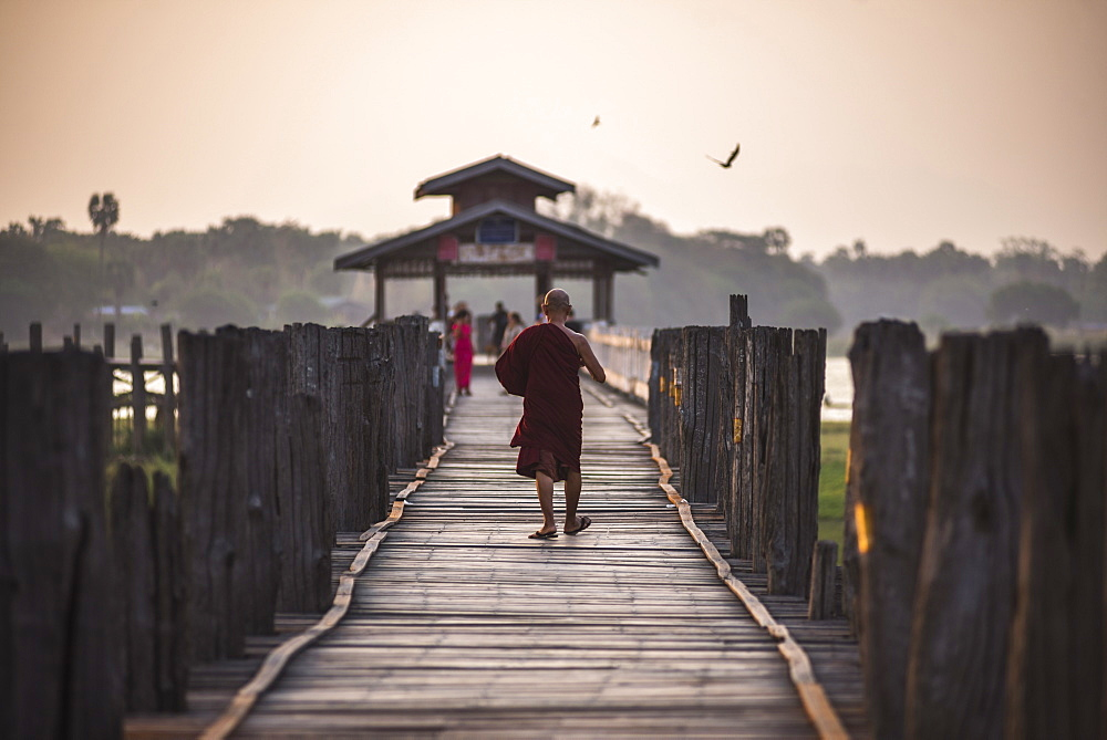 Buddhist Monk on U Bein Teak Bridge at sunrise, Mandalay, Mandalay Region, Myanmar (Burma), Asia