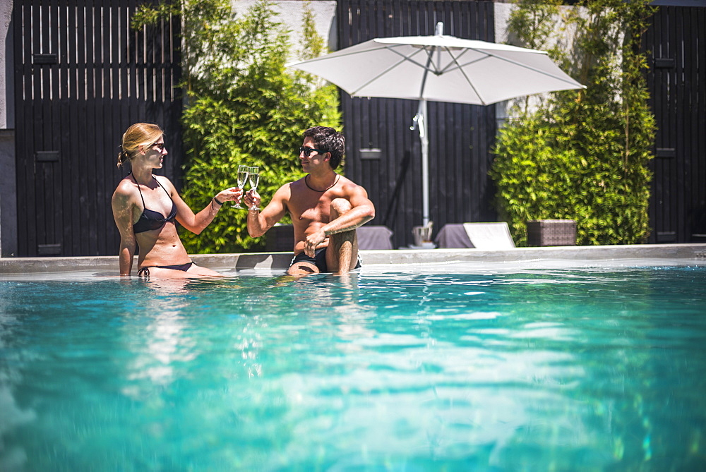 Couple on holiday, having drinks by a swimming pool, Santiago, Chile, South America