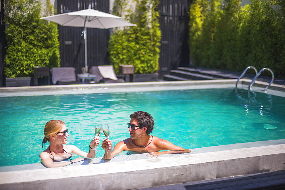 Couple on holiday, having champagne in a swimming pool, Santiago, Chile, South America