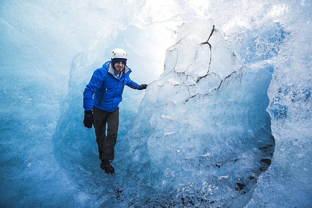 Tourist exploring an ice cave on Breidamerkurjokull Glacier, Vatnajokull Ice Cap, Iceland, Polar Regions