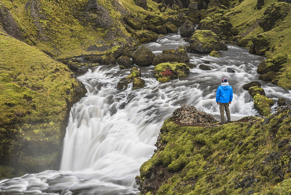 Tourist at a waterfall on the hiking trail above Skogafoss Waterfall, Skogar, South Region (Sudurland), Iceland, Polar Regions