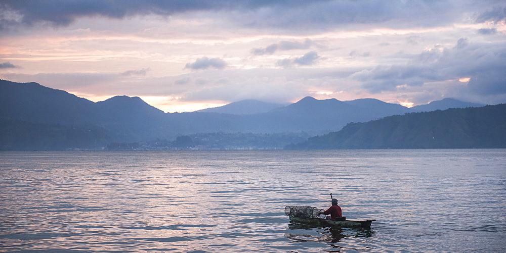 Fisherman in a fishing boat on Lake Toba (Danau Toba) at sunrise, North Sumatra, Indonesia, Southeast Asia, Asia