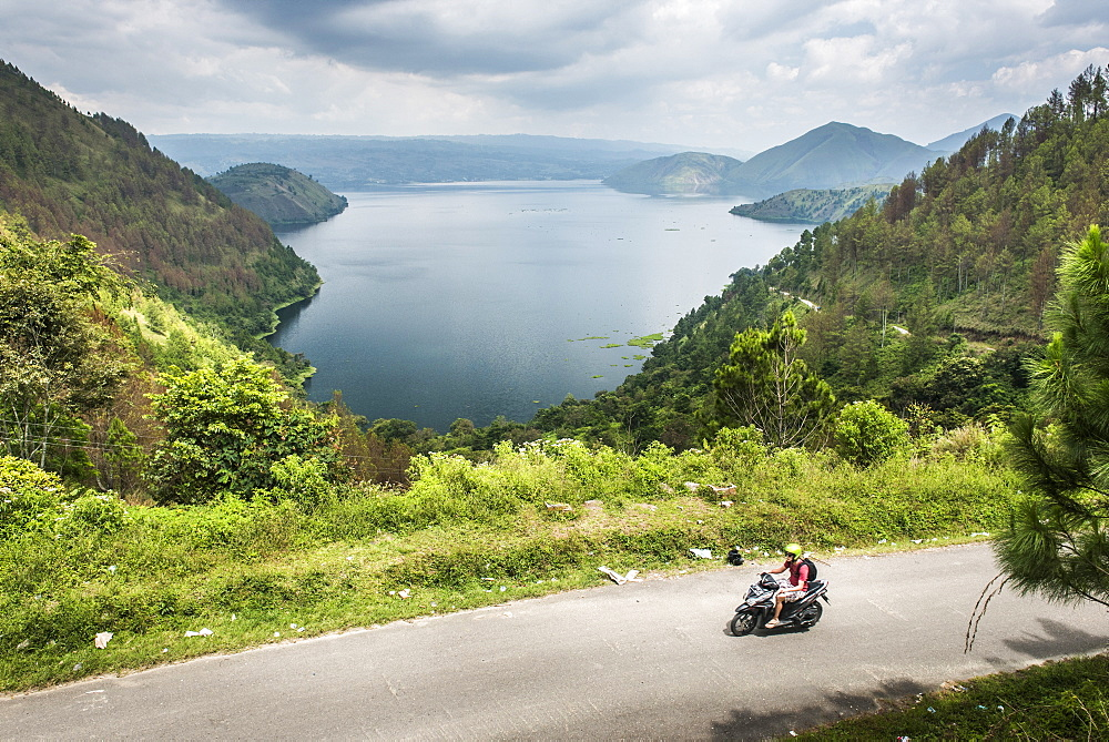 Tourist exploring Lake Toba (Danau Toba) by motorcycle, North Sumatra, Indonesia, Southeast Asia, Asia