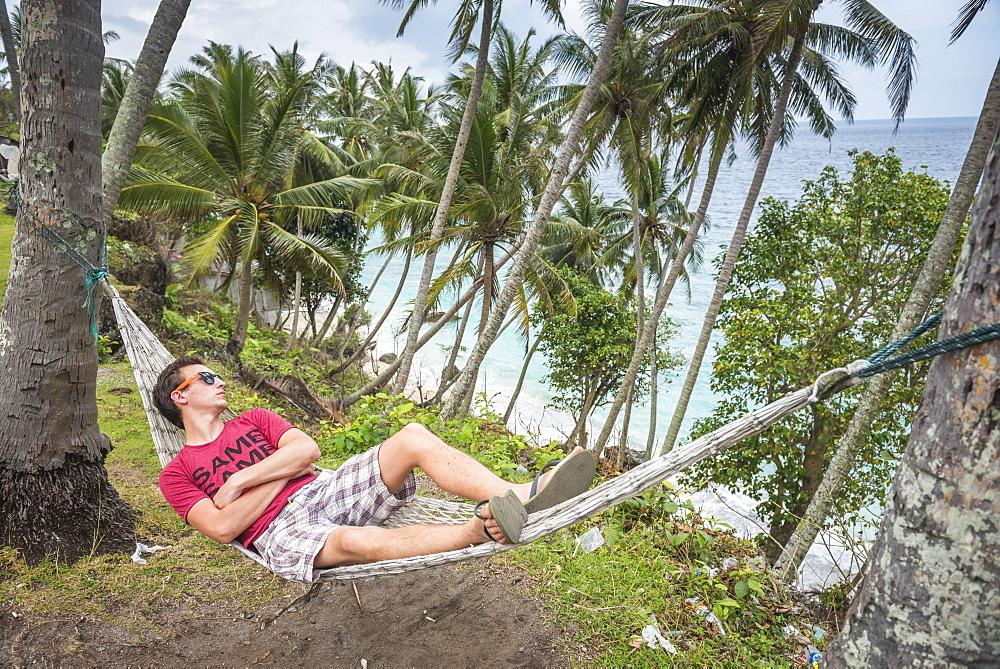 Tourist in a hammock at the beach, Pulau Weh Island, Aceh Province, Sumatra, Indonesia, Southeast Asia, Asia
