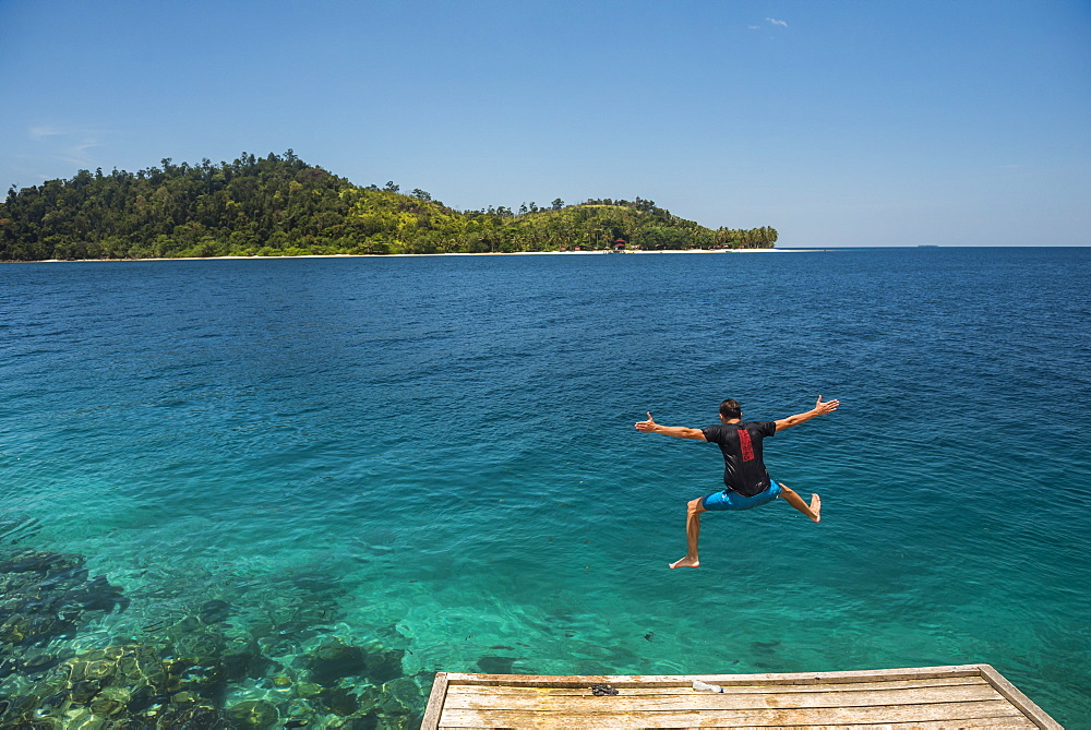 Tourist jumping into the Pacific Ocean at Twin Beach, a tropical white sandy beach near Padang in West Sumatra, Indonesia, Southeast Asia, Asia