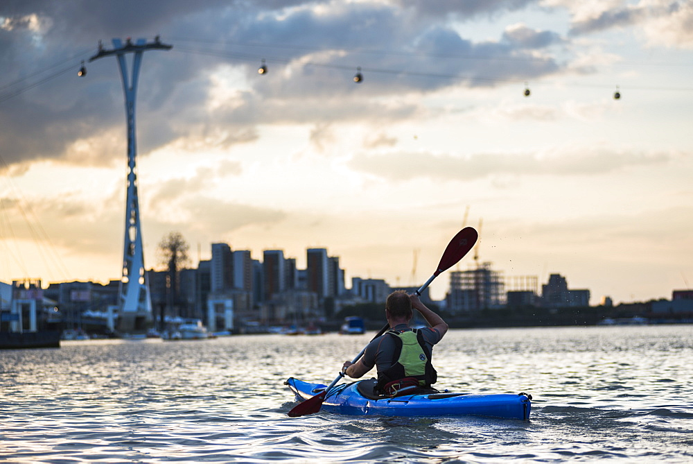 Kayaking at sunset under the Emirates Air Line Cable Car across the River Thames, Greenwich, London, England, United Kingdom, Europe