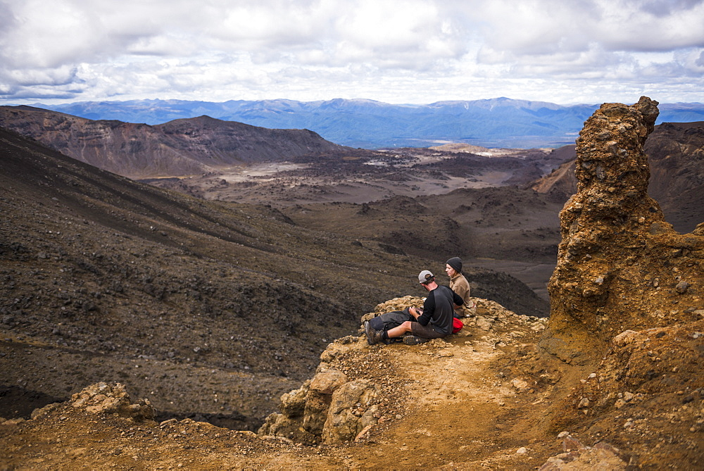 Couple resting on the Tongariro Alpine Crossing, Tongariro National Park, UNESCO World Heritage Site, North Island, New Zealand, Pacific