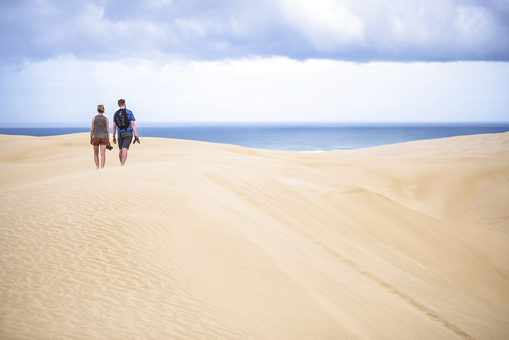 Two tourists at Te Paki Sand Dunes on 90 Mile Beach, Northland, New Zealand, Pacific
