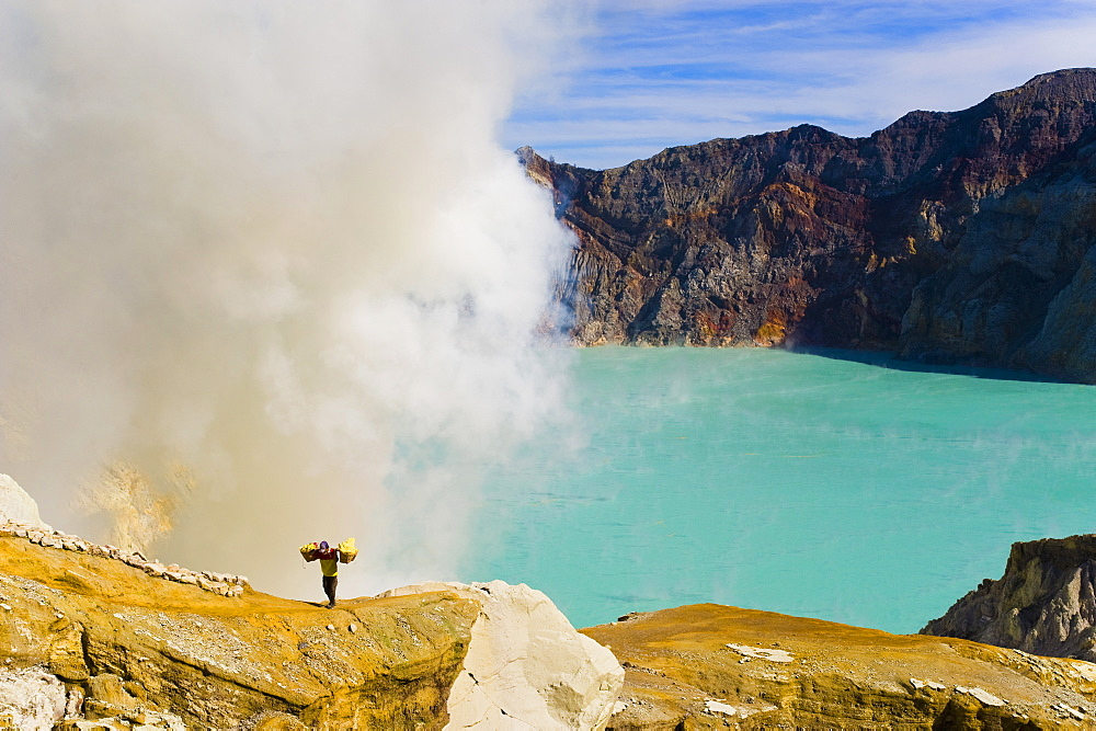 Sulphur worker appearing out of toxic fumes at Kawah Ijen, East Java, Indonesia, Southeast Asia, Asia