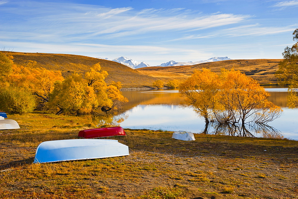 Rowing boats and snow capped mountains at Lake Alexandrina, Southern Lakes, Otago Region, South Island, New Zealand, Pacific