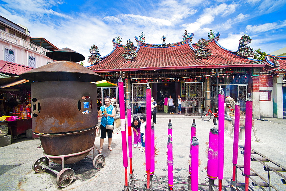 Malaysian people praying behind large incense sticks at a Buddhist temple in George Town, Penang, Malaysia, Southeast Asia, Asia